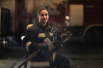 female firefighter portrait wearing full equipment, oxygen mask, and an axe. smoke and fire trucks in the background.