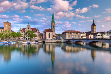 Wall Mural - Famous Fraumunster and St Peter church with reflections in river Limmat at sunrise in Old Town of Zurich, the largest city in Switzerland