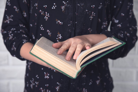 young woman hand holding green book