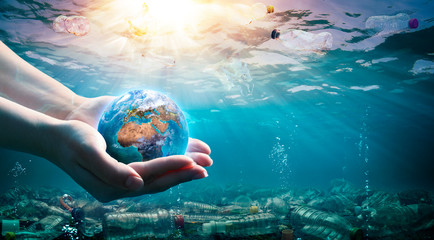 Plastic Waste In The Environment - Ocean Pollution - Hands Holding Earth - elements of this image furnished by NASA