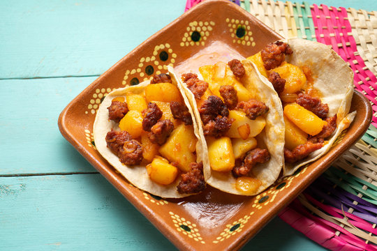 Mexican chorizo with potatoes tacos on turquoise background