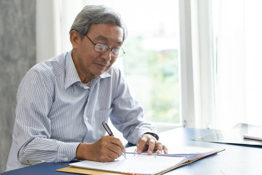 Asian smart business elder writing document report in the office.