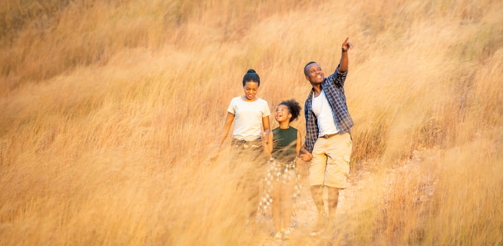 Portrait of Happy young African family father, mother and daughter hiking and holding hands together with smiling face. Relaxing family  parents and child walking together on golden meadow on mountain