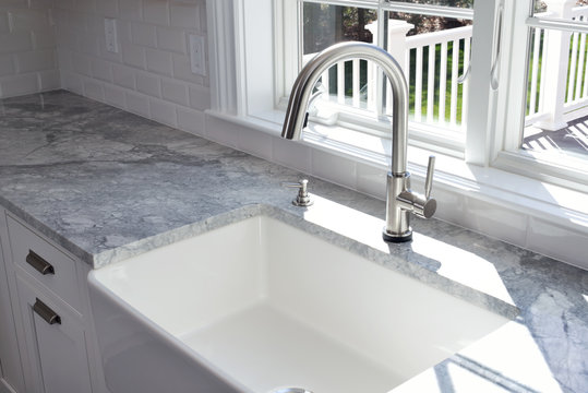 Modern kitchen sink and single handle brass faucet with soap dispenser, marble countertop and window to the garden.