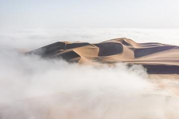 Top of a massive sand dune emerging from a thick cloud of fog after sunrise. Liwa desert, Abu Dhabi, United Arab Emirates.