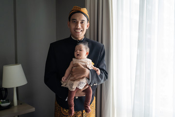 Asian man wearing traditional clothes and carrying little daughter,beskap is traditional heritage clothes from Java,Indonesia Fotomurales