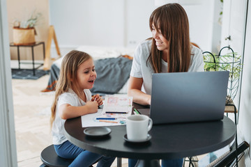 Working mom freelancer on the laptop with little daughter playing on table together at home
