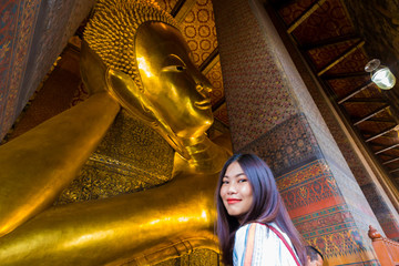 Wall Mural - Asian cute women travel in golden reclining buddha statue indoor temple pagoda