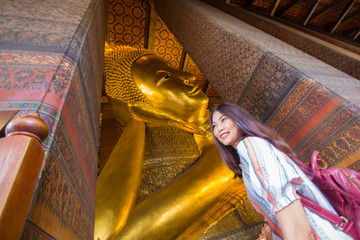 Fototapete - Asian cute women travel in golden reclining buddha statue indoor temple pagoda