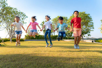 Canvas Prints Pistachio Large group of happy Asian smiling kindergarten kids friends holding hands playing and jumping together during a sunny day in casual clothes at city park.