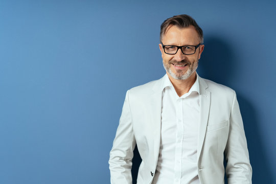 Smiling middle age man in glasses on blue