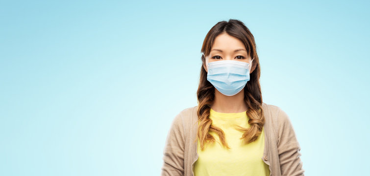 health, safety and pandemic concept - asian young woman wearing protective medical mask for protection from virus disease over blue background