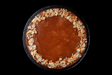 Modern pastry. Chocolate cake with nuts, almonds and peanut butter. Cake on a black background. background image, copy space text