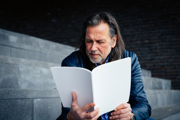 Older man with beard and long grey hair sits on a staircase and reads a magazine with a blank cover