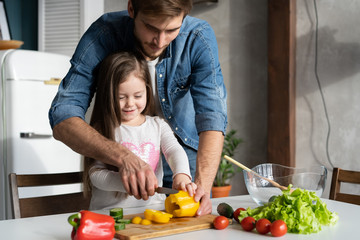 Handsome man and his little cute daughter are cooking on kitchen. Making salad. Healthy lifestyle concept. Fototapete