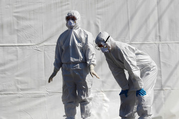 Medical workers in protective gear stand at a screening facility for checking coronavirus disease (COVID-19) in Cheongdo county