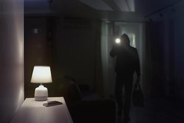 Burglar inside of a house with flashlight