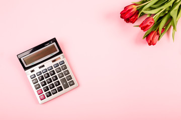 Holiday or victory in business or science. Red tulips on a pink background with a calculator are a background for advertising, a screensaver or visualization of a blog with free space for text.