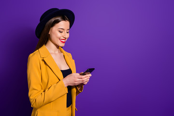 Fototapete - Turned photo of positive cheerful girl blogger use her smartphone read social network news follow posts enjoy wear yellow blazer bright headwear isolated over violet color background