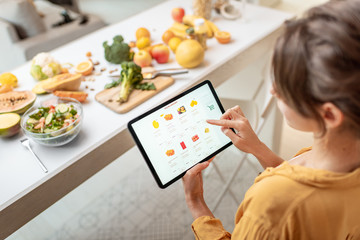 Photo sur Plexiglas Magasin alimentation Woman shopping food online using a digital tablet at the kitchen. Concept of buying online using mobile devices