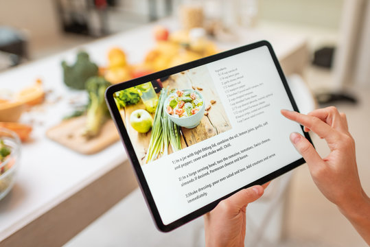 Woman looking on the digital recipe, using touchscreen tablet while cooking healthy meal on the kitchen at home, close-up view on the screen