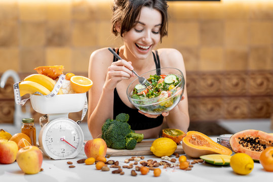 Sports woman eating salad, standing with lots of healthy fresh food on the kitchen. Concept of losing weight, sports and healthy eating
