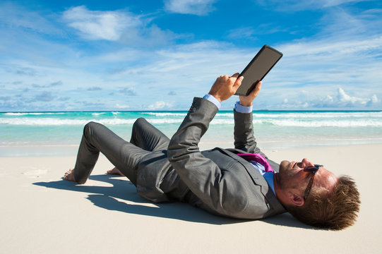 Relaxed office worker lying in a suit with his tablet on the shore of a tropical beach
