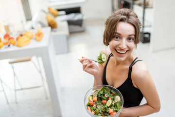 Portrait of a cheerful athletic woman eating healthy salad during a break at home. Concept of losing weight, sports and healthy eating
