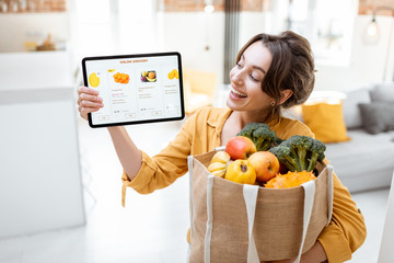 Papiers peints Cuisine Happy woman holding a digital tablet with launched online store while standing with shopping bag full of fresh products at home. Concept of buying online using mobile devices