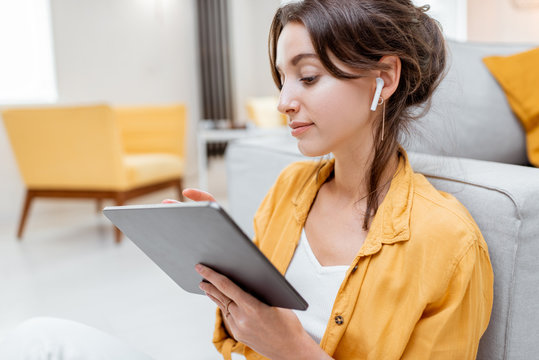 Young and cheerful woman working on digital tablet using wireless earphones while sitting relaxed at home. Concept of leisure, freelance and mobile work