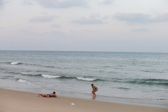 A couple plays on a beach which is usually full of tourists, amid fear of coronavirus in Phuket