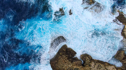 Fotorollo Himmelblau Wild Ocean water from above - Waves hitting the rocks - aerial photography