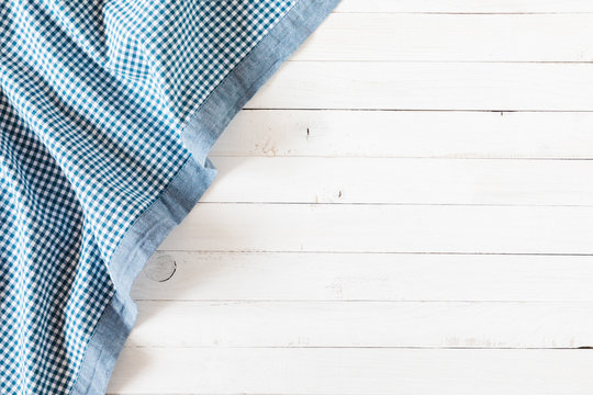 White old vintage wooden table with blue linen  checkered tablecloth. Flat lay, top view, copy space
