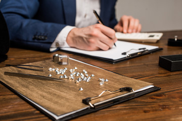 Selective focus of gemstones and tools near jewelry appraiser writing on clipboard on table isolated on grey