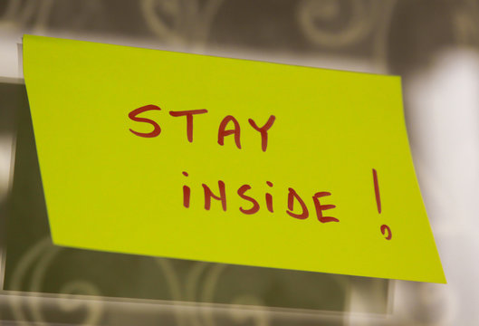 Sticky note on window with Stay Inside writing text message