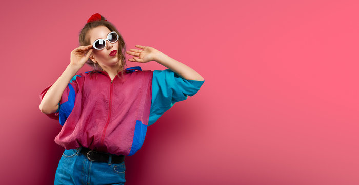 Cool teenager. Fashionable DJ girl in colorful trendy jacket and vintage retro sunglasses enjoys style of 80s � 90s vibes. Teenager Girl at disco party. Young fashion model on coral red background.