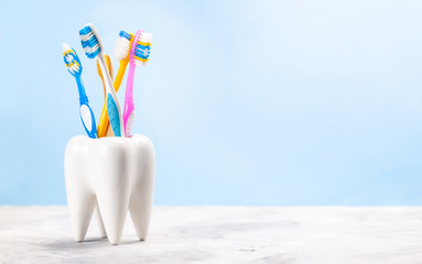 Many toothbrushes in a glass in the form of a tooth. Blue background. The concept of how to choose the right toothbrush