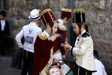 Ultra-Orthodox Jewish children smoke as they are dressed-up in costumes during celebrations marking the Jewish holiday of Purim in Jerusalem's Mea Shearim neighbourhood