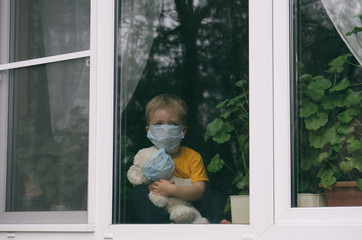 Child wearing face mask hugs teddy bear