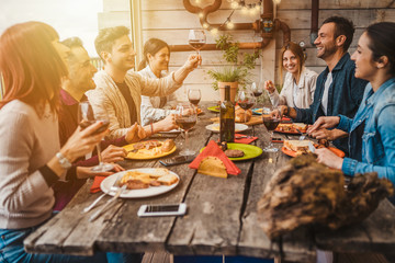 Group of young people having lunch on a terrace of an apartment at sunset - Millennials have fun together on a day of celebration