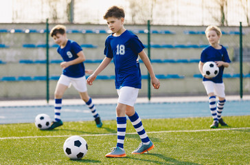 Soccer Training Exercises for Kids. Boys Training with Balls on Summer Football Grass Field. Young Sporty Kids in a Team with Coach. Practice Soccer Unit for School Children. Stadium in the Background