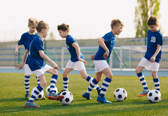 Kids Sports: Teaching Children to Improve Soccer Skills. Football camp for kids. Boys practice dribbling in field. Players develop skills. Children training with balls. Soccer slalom drills