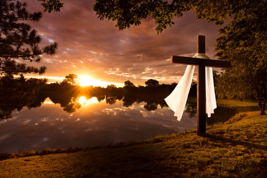Beautiful photo illustration of an Easter morning sunrise on a cross by a calm lake. The warm light almost announces Jesus's rising from the dead.