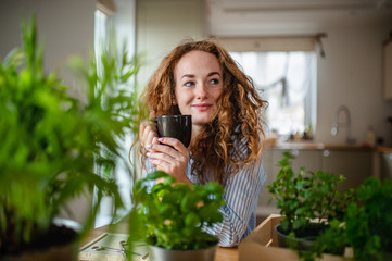 Young woman relaxing indoors at home with cup of coffee or tea.