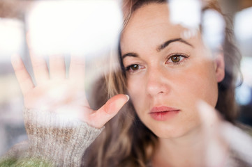 Young sad and depressed woman indoors by window at home.