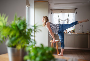 Young woman relaxing indoors at home, stretching.