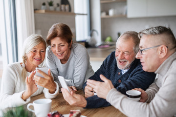 Group of senior friends at home, using smartphones.