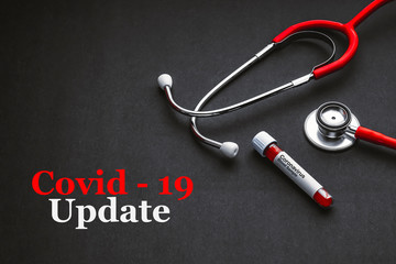 COVID 19 UPDATE text with stethoscope and blood sample vacuum tube on black background. Covid or Coronavirus Concept