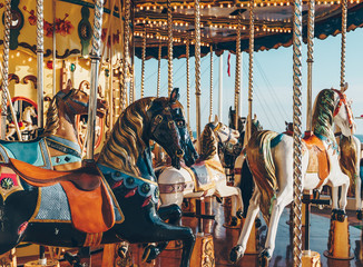 carousel in an amusement holiday park. Merry-go-round with horses on a fairground vintage carousel. Fotobehang