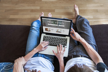 real estate concept on screen of computer, couple looking for apartment to rent or buy